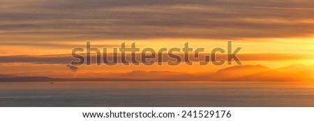 Golden clouded sunset on sea horizon - stock photo