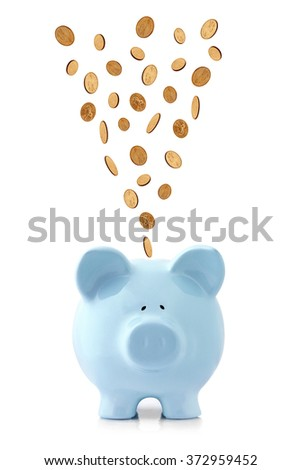 Golden coins falling into a blue piggy bank, isolated on white.  US dollar coins - stock photo
