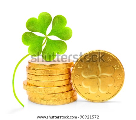 Golden coins with four leaf clover on a white background. - stock photo