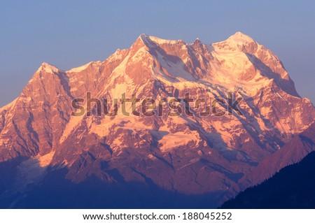 "golden color of Mountain 'Chaukhambha"" during sunset - stock photo"