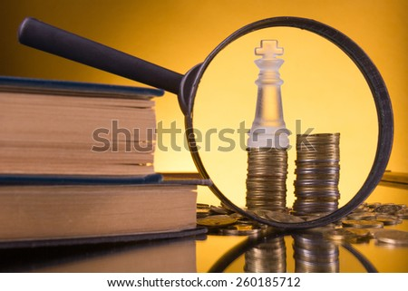 Golden columns of coins on yellow background with magnifying glass and books. Copy space. Banking. Go to Bank. Growth - stock photo