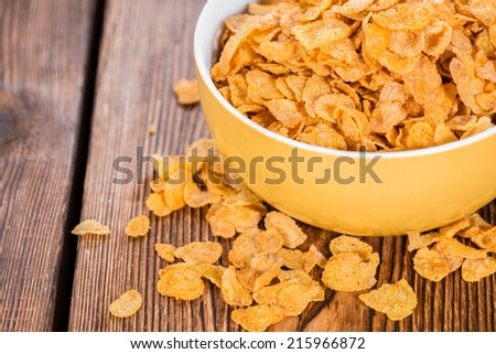 Golden Cornflakes (detailed close-up shot) on an old wooden table - stock photo