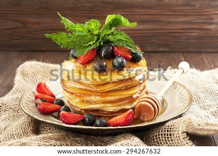 Golden crepes with strawberries  and blueberry - stock photo