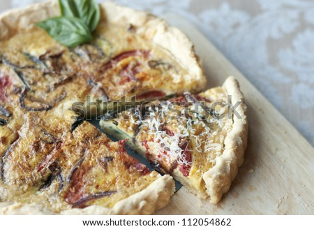 Golden crusted quiche with heirloom tomatoes, onions and herbs - stock photo