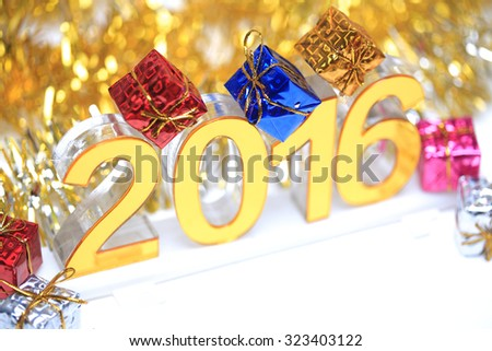 Golden 2016 3d icon with gift box in the christmas ornaments golden tinsel defocused blur backgrounds