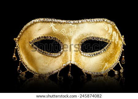 Golden decorated carnival mask with reflections on black - stock photo