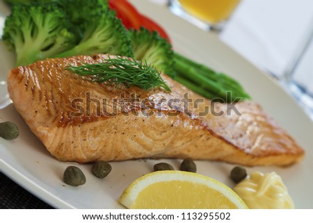 Golden delicious salmon steak with broccoli, asparagus, red pepper, capers, mayo and lemon - stock photo