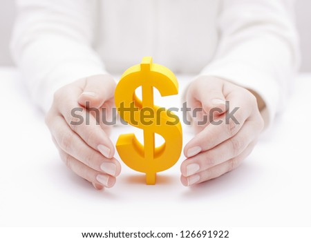 Golden dollar symbol protected by hands - stock photo