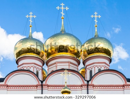 Golden domes of Russian orthodox church in Valday monastery against the blue sky - stock photo