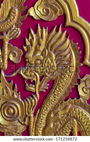 Golden Dragon Head on Red wood door - stock photo