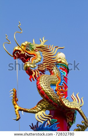 Golden dragon statue on red pillar in Chinese temple