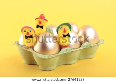 Golden Easter eggs and chicks in carton over yellow background