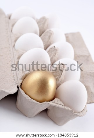 Golden egg and jast eggs in a cardboard box on a white background - stock photo