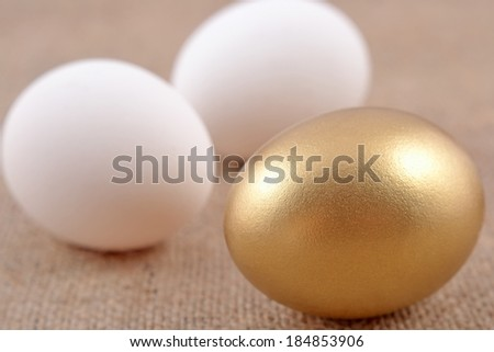 Golden egg and jast eggs on a sacking background - stock photo