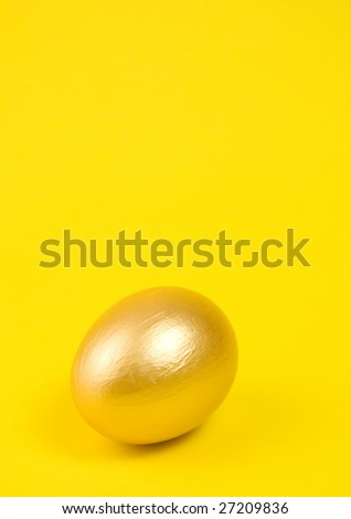 Golden egg on yellow background. Lots of space for text. - stock photo