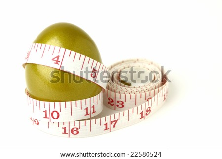 Golden egg with measuring tape - stock photo
