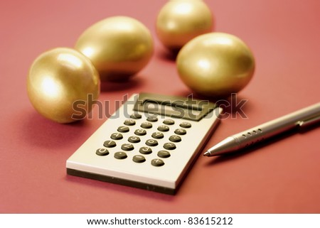 Golden Eggs with Calculator and Pen on Red Background - stock photo