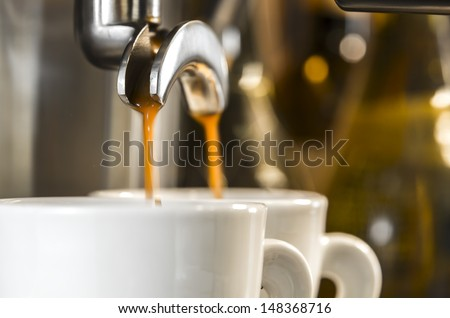 golden espresso flowing into the white porcelain cups - stock photo