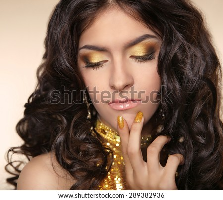 Golden eye makeup eyeshadows. Beauty Brunette woman with curly hair and manicured nails over beige background. - stock photo