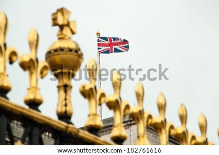 golden fence of buckingham palace with british flag - stock photo