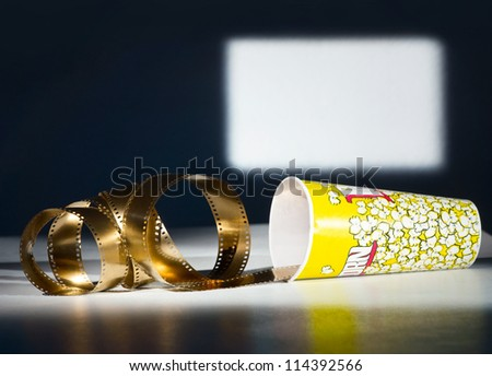 Golden film and paper cup for popcorn on screen background - stock photo