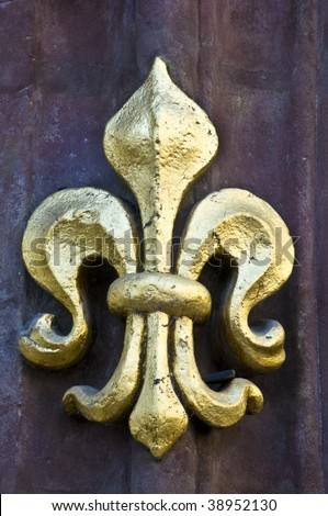 golden fleur de lis on a facade - stock photo