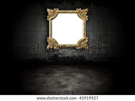 Golden frame in a dark room - stock photo