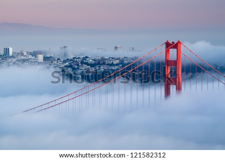Golden Gate at dawn surrounded by fog - stock photo