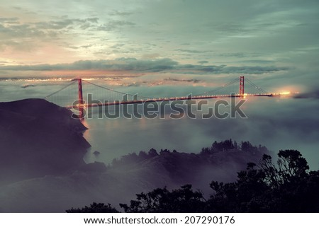 Golden Gate Bridge and fog in San Francisco in early morning - stock photo
