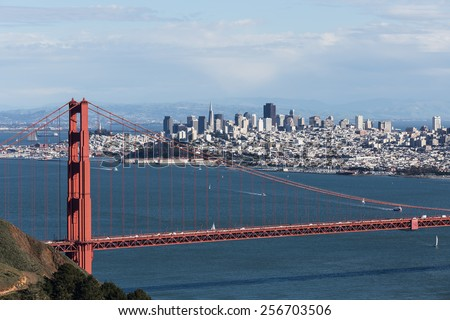 Golden Gate bridge and San Francisco looking south with blue water and sky partially obscured by clouds - stock photo