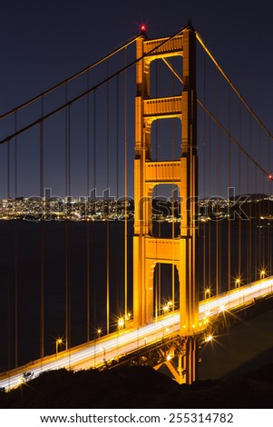Golden Gate bridge at night looking south with dark sky and bay and lights of San Francisco on background. Closeup vertical view on illuminated north tower of the bridge. - stock photo