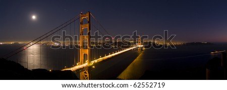 Golden Gate Bridge from the Marin Headlands with the moon reflecting on the San Francisco Bay. - stock photo