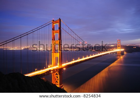 Golden Gate Bridge glows against backdrop of illuminated Bay Bridge and San Francisco skyline.