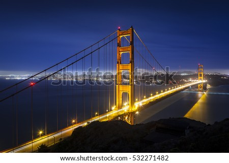 Golden Gate Bridge in San Francisco, California at night with traffic light trails.