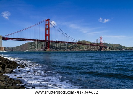 Golden Gate Bridge in San Francisco California from Fort Point National Historic Site waterfront park on sunny blue sky morning - stock photo