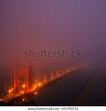 Golden gate in the mist at night - stock photo