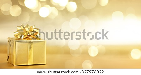 Golden gift box on abstract background - stock photo