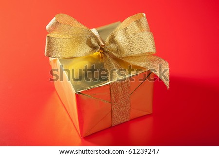 golden gift box over red background - stock photo