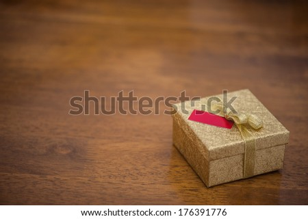 Golden gift box with bow and a small card on a wooden table - stock photo