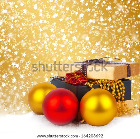 Golden gift box with Christmas balls and garlands of beautiful beads on abstract  background - stock photo