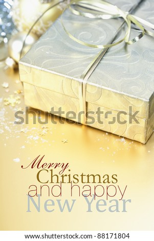 Golden gift box with golden ribbon and christmas decorations