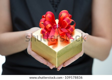 Golden gift box with red and orange satin bow on hand - stock photo