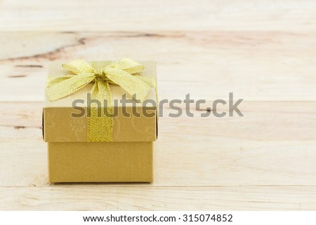 Golden gift box with ribbon bow on wooden table. - stock photo