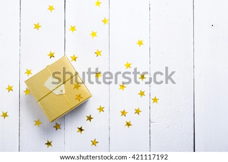 golden gift box with star shape decor on white wood table background - stock photo