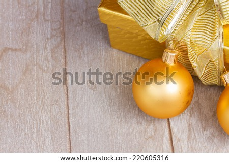 golden  gift box with with christmas decorations on wooden background with copy space