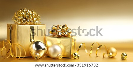 Golden gift boxes with decoration on abstract background - stock photo