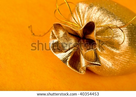 Golden gift sack over orange background - stock photo