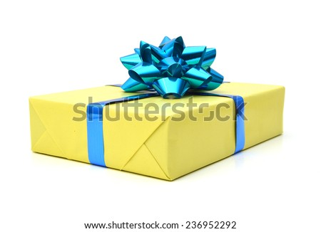 Golden gift wrapped present with blue ribbon bow isolated on white  - stock photo