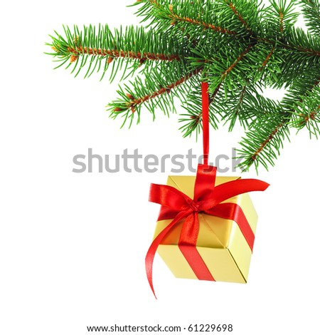 Golden gift wrapped present with red satin ribbon bow hanging on a green spruce branch - stock photo