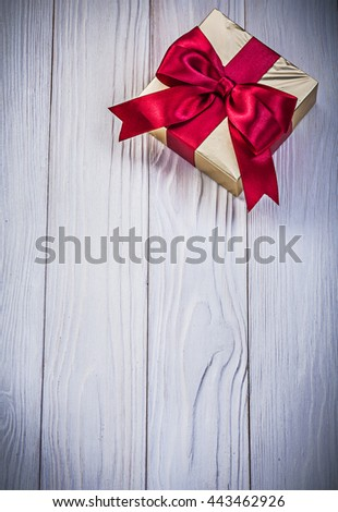 Golden giftbox with present on wood board holidays concept. - stock photo